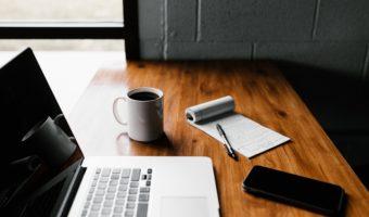 Schreibtisch mit Laptop, Kaffee und Smartphone
